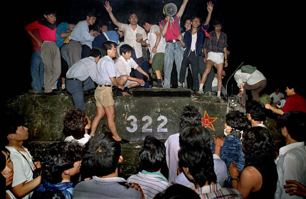 Civilians hold rocks as they stand on a government armored vehicle near Chang'an Boulevard in Beijing, early June 4, 1989, before the army began a crackdown on pro-democracy protesters in and around Tiananmen Square.