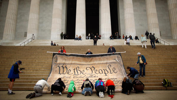 Volunteers at the Lincoln Memorial help roll up a giant banner printed with the Preamble to the Constitution during an October 2010 demonstration against the Supreme Court's <em>Citizens United</em> ruling.