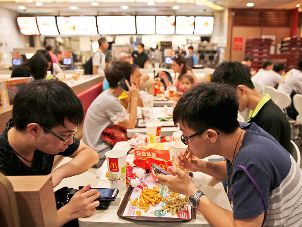Customers eat at a McDonald's restaurant in Hong Kong on Friday. McDonald's restaurants in Hong Kong have taken chicken nuggets and chicken fillets off the menu after a U.S.-owned supplier in mainland China was accused of selling expired meat.