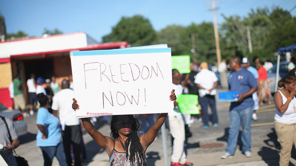 A Demonstrator protesting the shooting death of teenager Michael Brown holds up a sign Wednesday in Ferguson, Missouri.