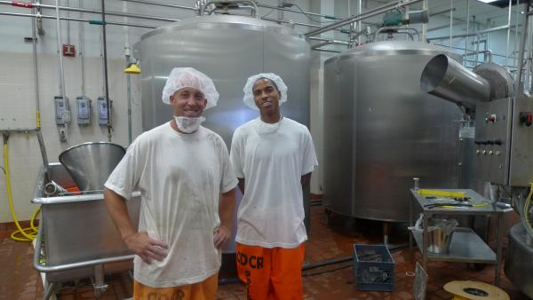 "Inside the secure perimeter in the milk processing facility at Corcoran state prison, Ryan Mons (left) and Edward Wilson give a tour. Wilson's job involves testing the milk for bacteria. ""I take pride in what I do,"" he says."