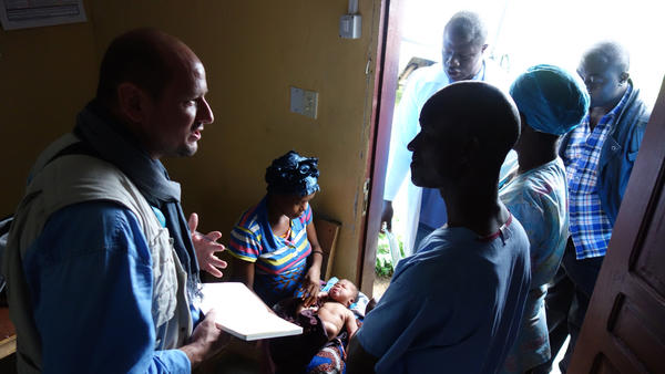 UNICEF officer Laurent Duvillier talks with families about getting vaccines at the Community Clinic in Louisiana Township.