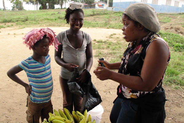 Siatta Scott Johnson (at right), who has guided NPR journalists through Liberia and its lingo, advises two girls on how best to carry bananas and bread.