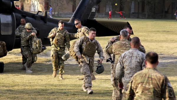 Capt. Casey Wolfe, Capt. John Urquhart, Staff Sgt. Ben Dellinger, Sgt. James Wright - arrive in Kabul as part of Operation Proper Exit for wounded warriors. They are all walking toward the camera. They are greeted by Gen. John Campbell, who is embracing Wright.