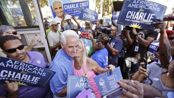 Florida Democratic gubernatorial candidate Charlie Crist, center, gets a kiss from a supporter after he stepped off his bus during a brief campaign stop at Delevoe Park in Fort Lauderdale, Fla., on Oct. 25.