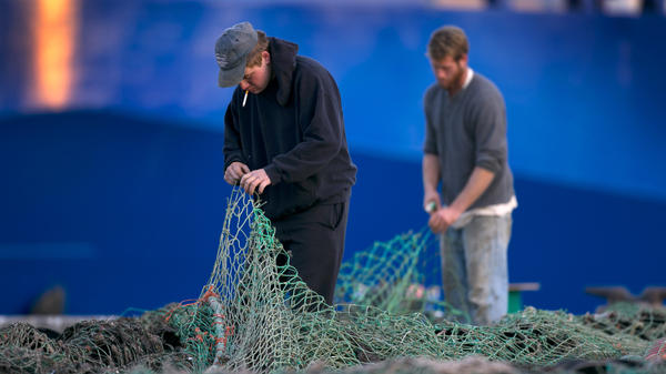 Fishermen Ed Stewart (left) and Tannis Goodsen mend groundfishing nets on Merrill Wharf, in Portland, Maine, last November.