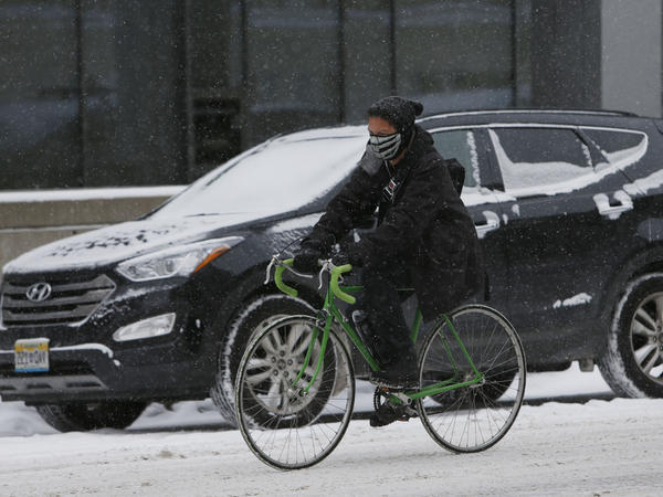 Traffic slowed in downtown Denver on Wednesday as snow fell on the city.