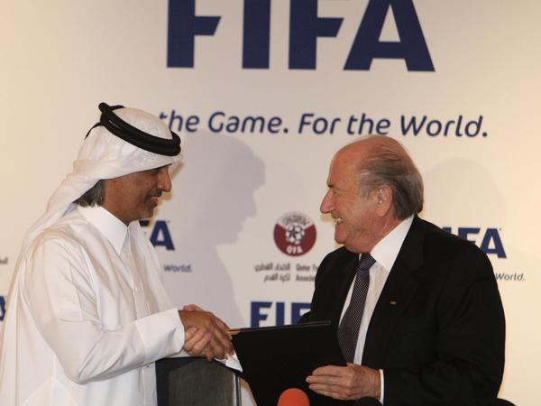 FIFA President Sepp Blatter and Qatar Football Association President Sheikh Hamad Bin Khalifa Bin Ahmed al-Thani exchange documents in Doha, Qatar, on Dec. 16, 2010, after the Arab country won the bid to stage the 2022 FIFA World Cup.
