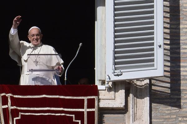 Pope Francis salutes the crowd from the window of the apostolic palace overlooking St.Peter's square during his Sunday Angelus prayer.