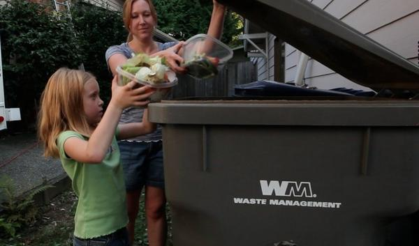 "Libby Mills, 7, helps her mom Sara Mills in dumping the family's food scraps into the yard waste container. Libby says, ""It's not very di fficult just to put something in a bin."""