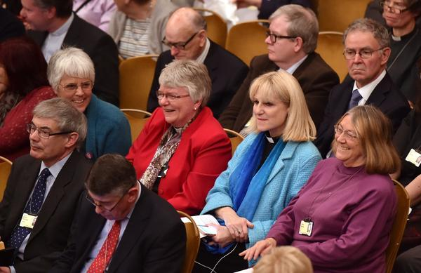Members of the Church of England's Synod react after a vote to formalize the approval of consecrating women as bishops in central London Monday. The Church of England's governing body on Monday adopted a historic measure allowing women to become bishops.