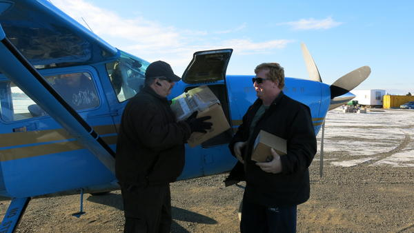 Bush pilot John Bouker (right) and village public safety officer Mike Myers (left) outside Bouker's Cessna 207. Bouker transports Alaskan cops to remote areas and helps pick up prisoners.