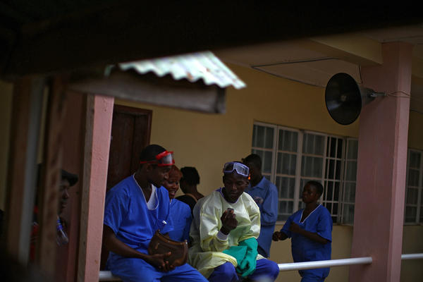 Support staff gather outside of the isolation buildings at Hastings Ebola Treatment Center in Freetown, Sierra Leone.