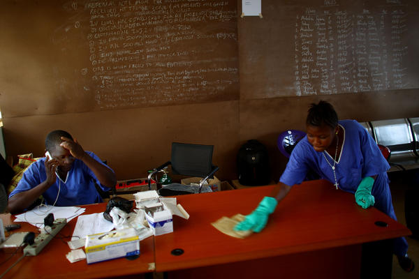 Dr. Komba Songu M'Briwah, left, talks on the phone while staff members disinfect offices at the Hastings Ebola Treatment Center in Freetown.