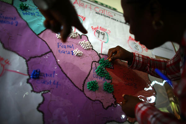 Workers add pins to a map showing the location of alert calls at the Western Area Emergency Response Center in Freetown, Sierra Leone. Hundreds of residents call the emergency line every day to report more possible cases in their neighborhoods.