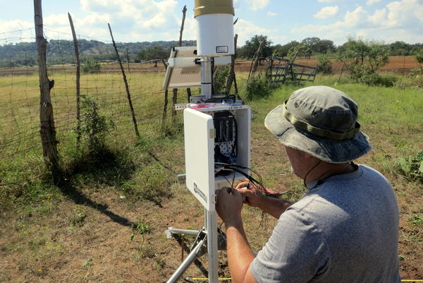 Workers calibrate a device that will measure the soil's moisture.