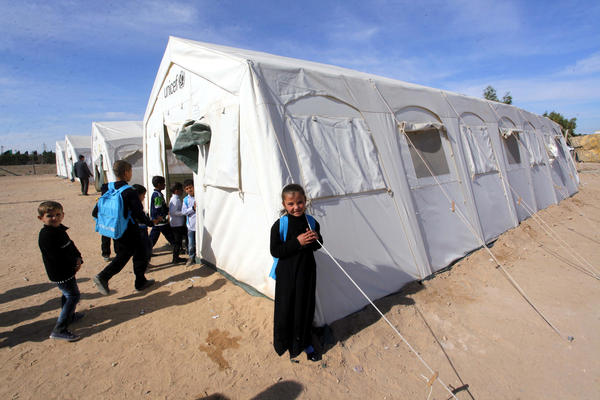 An Iraqi child, whose family fled from Islamic State violence in the northern city of Mosul, stands outside a tent that serves as a school in the southern city of Najaf on Sunday. Some 2 million Iraqis have been driven from their homes by fighting this year.