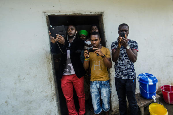 Folks in Monrovia photograph the body collector team.