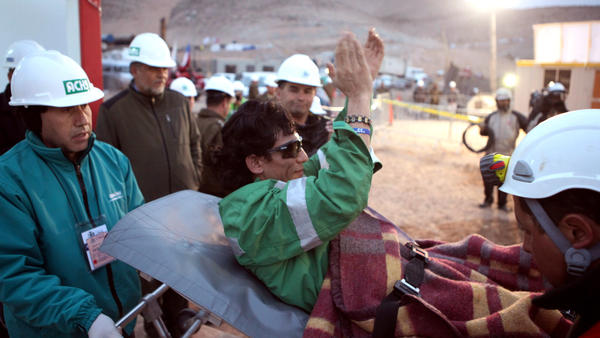 Miner Claudio Yanez applauds as he is carried away on a stretcher after being rescued from the collapsed San Jose mine where he had been trapped with 32 other miners for over two months in 2010 near Copiapo, Chile.