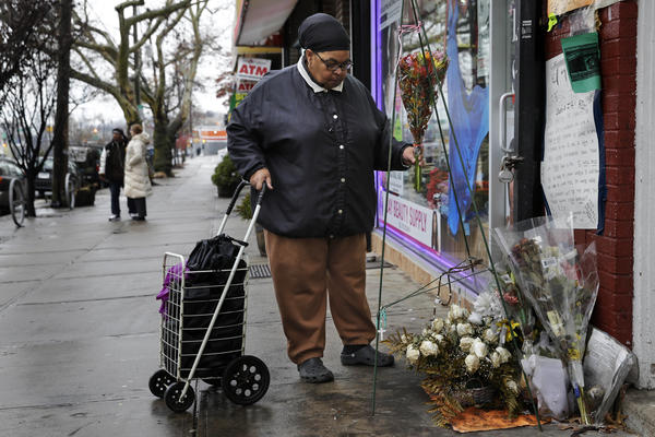 """A woman places flowers at a memorial for Eric Garner near the site of his death. Citing """"centuries of racism that have brought us to this day,"""" New York Mayor Bill de Blasio said the fact that protesters have rallied around the statement """"black lives matter"""" reflects a sad situation."""