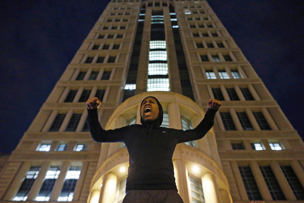 A protester at the U.S. Courthouse in St. Louis, Mo., chants slogans against the grand jury decision in the Garner case and police violence. Garner's family called for peaceful protests.