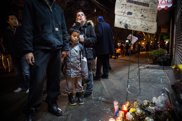 """Robert Corulla and Crystal Demaio stand with their son, Edward Corulla, during a vigil for Garner. The encounter between Garner and Pantaleo caused an uproar after video footage of the incident was released. It showed Garner repeatedly gasping """"I can't breathe"""" as Pantaleo and other officers took him to the ground."""
