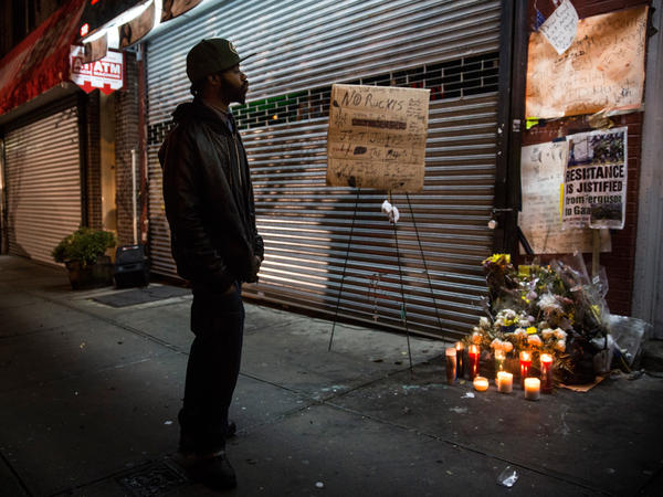 A man pauses Wednesday at a memorial for Eric Garner outside the beauty salon in Staten Island where he died during an arrest attempt.