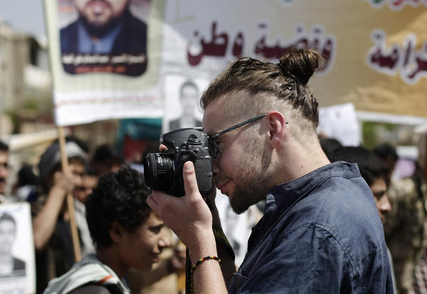 "Luke Somers, 33, an American photojournalist who was kidnapped more than a year ago by al-Qaida, photographs a demonstration in Yemen in 2013. Somers and a South African teacher held by al-Qaida militants in Yemen were killed Saturday during a U.S.-led rescue attempt, a raid President Obama said he ordered because of an ""imminent danger"" to the reporter."
