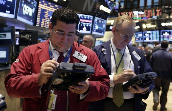 Trader Michael Capolino, left, works on the floor of the New York Stock Exchange Tuesday, Aug. 13, 2013. Stocks are inching mostly higher in early trading on Wall Street after the government reported a pickup in retail sales last month. (Richard Drew/AP)