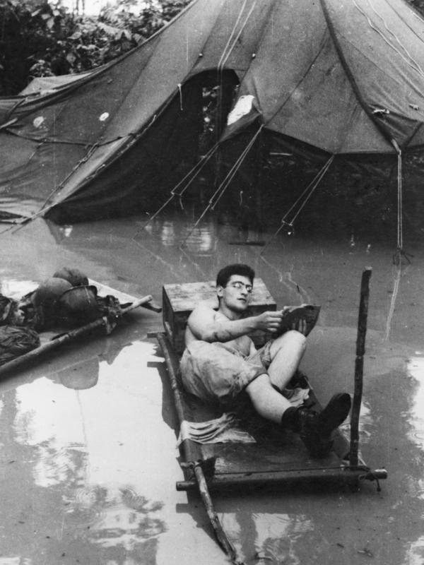 A soldier reads an Armed Services Edition in monsoon conditions during World War II.