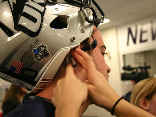 A tiny sensor is placed behind the ear of a University of New Hampshire football player. These sensors track the force and frequency of hits to the head during play.