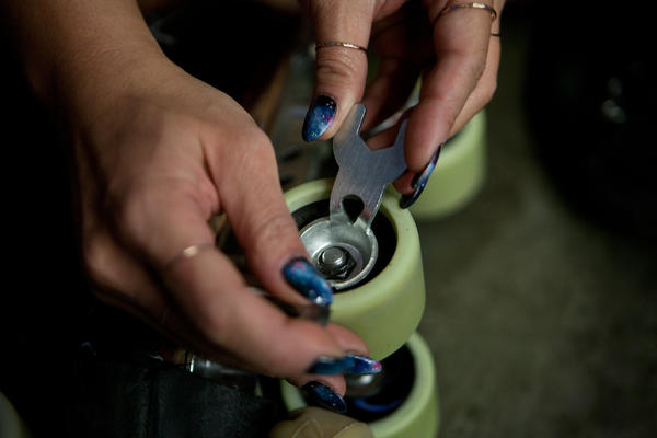 Park tightens the wheels on her skates in preparation for the roller derby bout. She's also a nail artist.