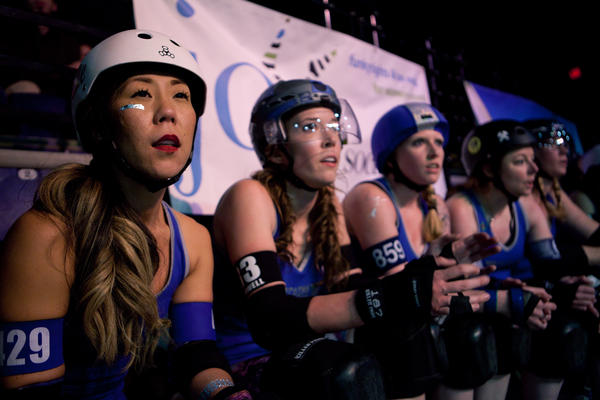 Elle L. Cool Jam (from left), Serenity Caldwell (Artoo Detoonate), Shayna Nestor (Shayna Nestor — she skates under her legal name), Candace Locke (Celia Casket) and Lisa Chenard (Bad Ass Mama) watch their teammates play.