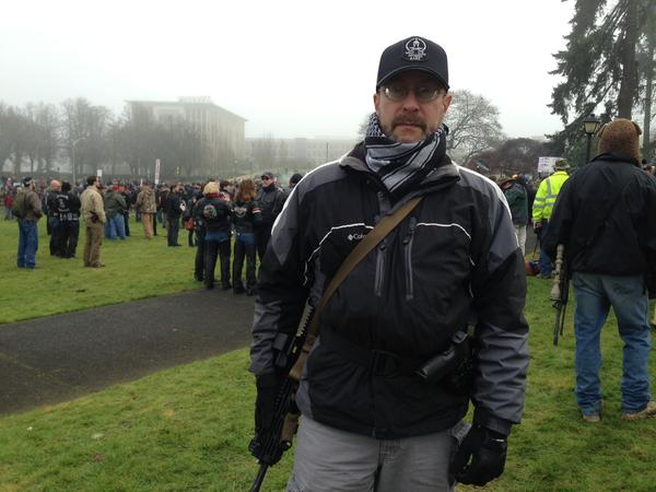 Dave Grenier allowed people to handle his handgun as an act of defiance against the new background check law. Grenier believes the law violates the Washington constitution.