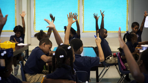 Students at KIPP Central City Primary School raise their hands during a social studies class on August 14, 2014 in New Orleans. The school's student body is nearly 100 percent black in a system that is 85 percent black.