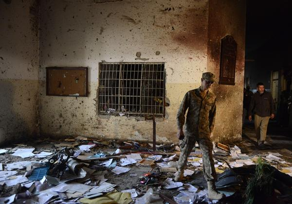 A Pakistani soldier walks amid the debris in an army-run school Wednesday, a day after Taliban militants attacked the school in Peshawar.