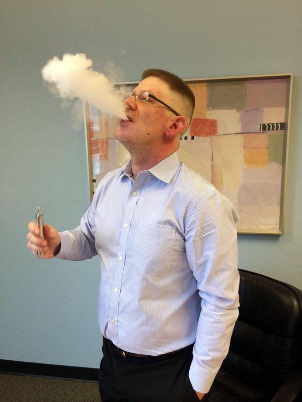 Justin Newman exhales vapor from an e-cigarette.