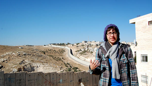 Amelia Wolf, an American Jewish student, stands near the gate of Al-Quds University, in the West Bank town of Abu Dis, where she studied last year. The wall behind her is part of the Israeli West Bank barrier that now separates Abu Dis from Jerusalem.