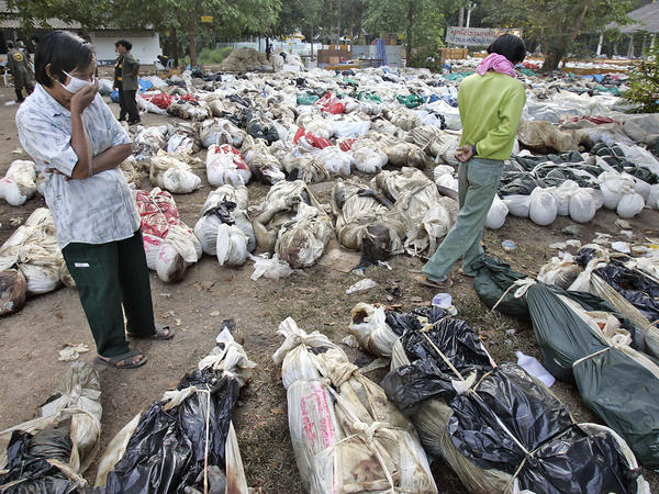On Dec. 30, 2004, Thais walk outside a Buddhist temple near Takuapa, Thailand, where more than 1,000 bodies had been gathered.