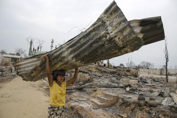 A Myanmarese girl carries away a burned tin roof from ruins in Meiktila, Myanmar. Sectarian violence between Buddhists and Muslims in March left more than 40 people dead, with large areas of the town completely destroyed by fires and looting.