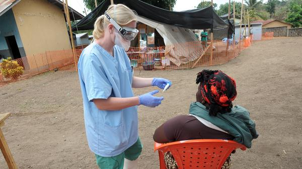A nurse of the 'Doctors without Borders' medical aid organisation examines a patient in the in-take area at a center for victims of the Ebola virus in Guekedou, on April 1, 2014. The viral haemorrhagic fever epidemic raging in Guinea is caused by several viruses which have similar symptoms — the deadliest and most feared of which is Ebola.