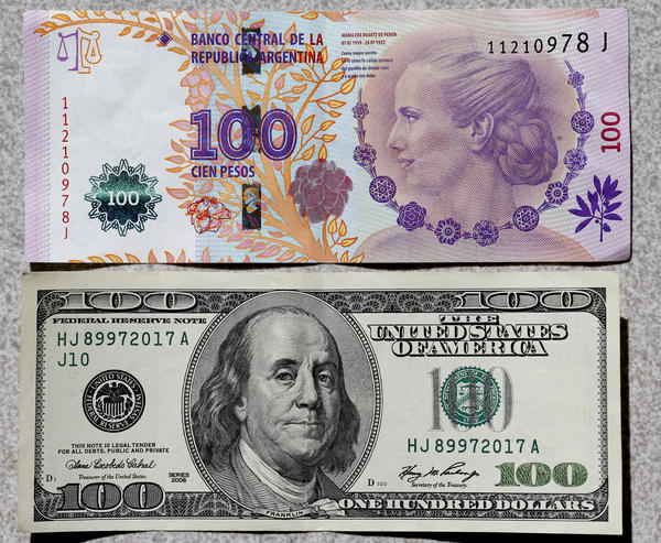 An Argentine 100 pesos bank note (top), featuring an image of former first lady Eva Peron, is displayed next to a U.S. $100 note. At the official rate, $1 is about 8.5 pesos. But the so-called blue-dollar rate – which is actually the black market rate — is about 13 pesos to the dollar.
