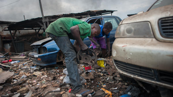 Kwesi Bido (left) and Inusa Mohammed stop to wipe bits of metal and dirt off the magnetic speakers they use to collect scrap in the rubble of the electronic waste dump at Agbogloshie, in Accra, Ghana.