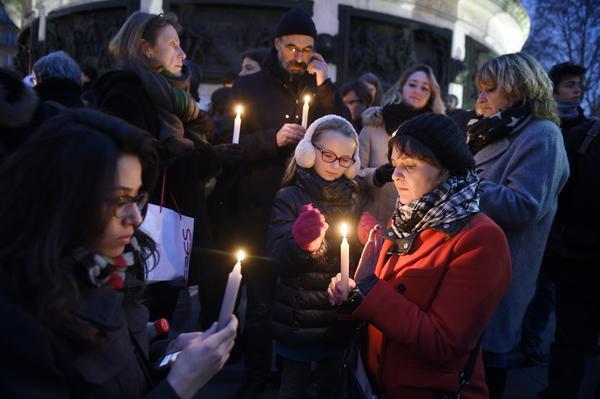 People light candles during a vigil at the Place de la Republique in Paris.