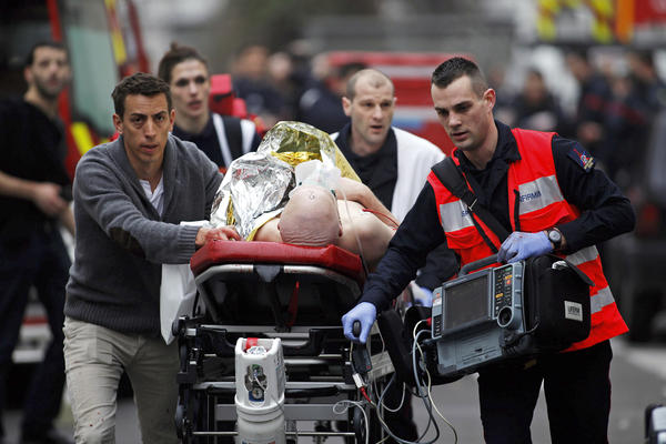 An injured person is evacuated outside the office Wednesday. In 2011, <em>Charlie Hebdo</em> was the target of a firebomb attack after it printed a drawing of the Prophet Muhammad.