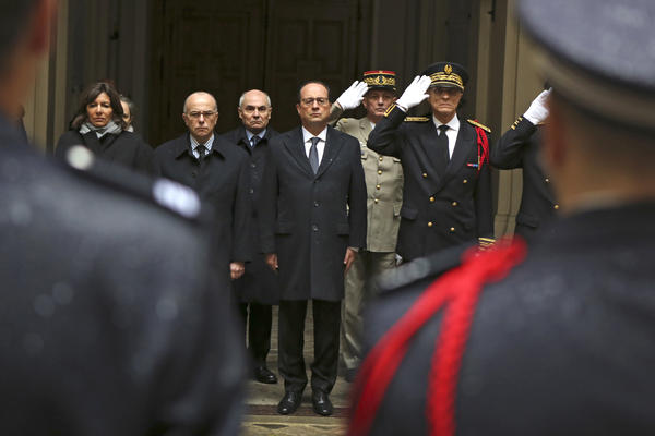 French President Francois Hollande (center) stands with French officials to observe a minute of silence at Paris Prefecture.