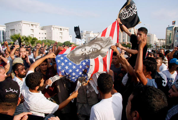 Tunisian protesters burn a U.S. flag bearing a portrait of actress Marilyn Monroe during a demonstration against the film <em>Innocence of Muslims</em> outside the U.S. Embassy in Tunis in September 2012. The anti-Islam film sparked protests at many U.S. embassies in the Muslim world.