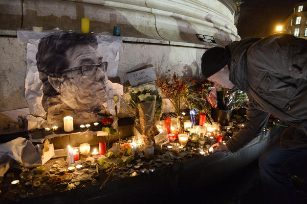 "A man lights a candle next to a picture of French cartoonist Bernard ""Tignous"" Verlhac during a rally at Republic Square in Paris on Thursday. The cartoonist was one of 12 people killed in an attack Wednesday on the headquarters of the satirical magazine <em>Charlie Hebdo</em>."
