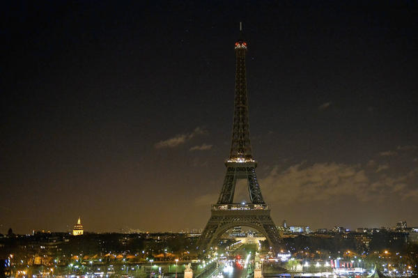 As a tribute for the victims of Wednesday's attack on the French satirical magazine <em>Charlie Hebdo </em>the lights of the Eiffel Tower were turned off for five minutes at 8 p.m. local time on Thursday. French authorities are searching for two brothers suspected in the attack.