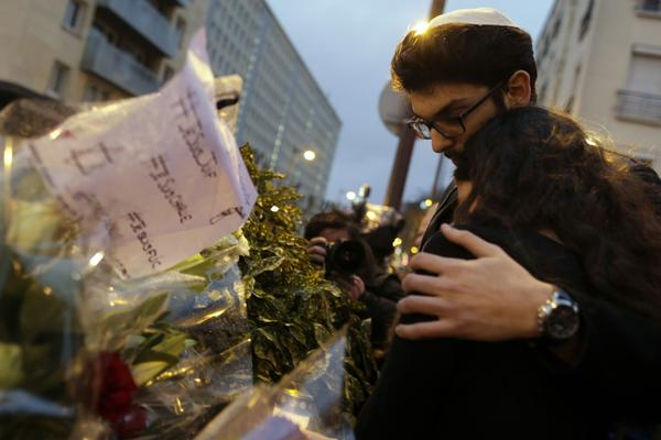 Mourners stand in front of flowers during a gathering at the end of Shabbat called by the Jewish Student's Union of France (UEJF) association on January 10, 2015, at the Porte de Vincennes in eastern Paris, in homage to the victims of a nearby hostage-taking drama in a Jewish supermarket during which five people were killed, including the hostage-taker, and four were left critically wounded before it ended with a police assault on January 9. (Kenzo Tribouillard/AFP/Getty Images)